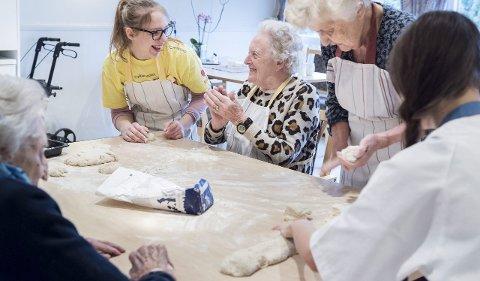 Det blir god stemning rundt bordet når det skal bakes boller. Videregående-elevene Nicoline Bjørstad og Ida Ninett Bjerkesmoen får god respons fra Ingeborg Kjelsås, Klara Sørstrøm og Astrid Myhre.
