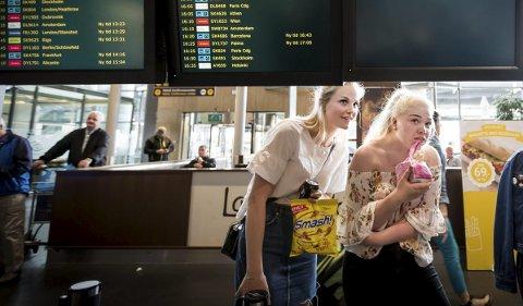 Bak skjermen med alle ankomsttidene forsøker to unge damer å gjemme seg. I hendene har de en stor pose smågodt og Smash. Det er nettopp dette jenta de venter på har savnet mest etter ett år i Australia.