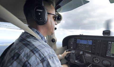 OVERVÅKER: Blikket til pilot Vegard Slettene i Grenland flyklubb beveger seg over terrenget. Han har god erfaring i å oppdage branner fra lufta. Foto: Bjørn Harry Schønhaug