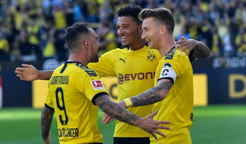 Dortmund's Marco Reus, right, celebrates with Dortmund's Jadon Sancho, center, and Dortmund's Paco Alcacer after he scored his side's second goal during the German Bundesliga soccer match between Borussia Dortmund and Bayer Leverkusen in Dortmund, Germany, Saturday Sept. 14, 2019. (AP Photo/Martin Meissner)