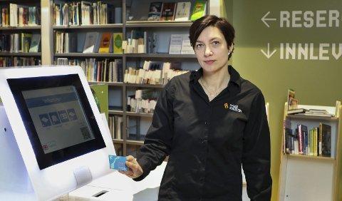 AUTOMAT: Biblioteksjef Mari Eeg ved automaten hvor brukerne registrer bøkene de låner og senere leverer.