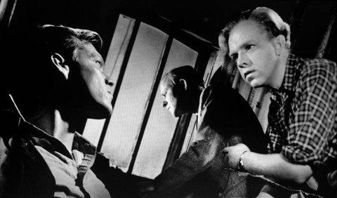 En scene fra Arne Skouens filmdrama om nødlandingen i Brunlanes. Flykapteinen, Jack Kennedy (t.v.), spiller seg selv i filmen. Henki Kolstad (t.h.) har hovedrollen.