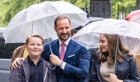 Kronprins Haakon, her avbildet sammen med prinsesse Ingrid Alexandra og prins Sverre Magnus, bør nok ta med paraplyen i Kristiansund på tirsdag.