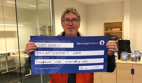 Daglig leder Geir Henning Waagsnes i Friluftsrådet Sør med sjekken fra Gjensidigestiftelsen, som sikrer sommerleirskoler i ni kommuner i distriktet i sommer.