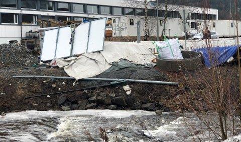 LØSEGJENSTANDER:Bilde fra elvebredden ved Mosenteret der det i vinter har vært lagret ymse byggevarer.