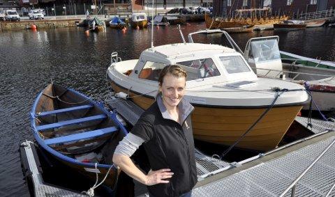 BÅTGLAD: Aina Christine Matre er leder for den nye Båtdeleringen i Sandviken. Her er kan du låne både den store motorbåten og oselveren som ligger i bakgrunnen for slikk og ingen ting. Nå håper hun på godt besøk under Sandvikdagene til helgen.FOTO: DAG BJØRNDAL