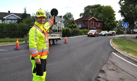 ASFALTERER: Tom Eriksen dirigerer trafikken på Borre i morgentimene tirsdag. Den siste puljen fikk passere klokka 06.05.