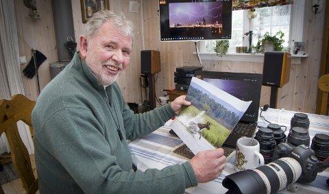 VINNER: Tor Øivind Løchen på hytta ved Storsjøen med «sommerens blinkskudd» i hendene. På skjermen i bakgrunnen er et av hans andre blinkskudd, bilde av lyn over skyskraperne i Dubai     han tok da han bodde der.
