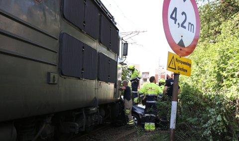 SKJÆRES UT: Bilen satt fast i toget, da toget rygget unna. Dermed måtte brannvesenet bistå med å skjære løs bilen.