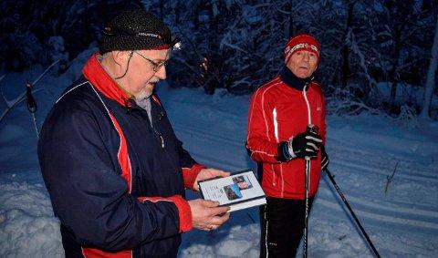 Jens Mørch viser fram et eksemplan av boka som er lagt ut i kasser ved alle de ni stasjonene mellom Dokka og Eina. Her kan turgåere langs jernbanen finne informasjon og skrive inn navnet sitt. T.h. turgåer Bjørn erik Edvardsen.