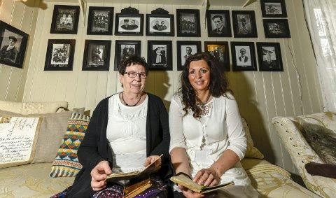 Historiefortellere: Agdis og Ann-Synnøve Albertsen har gravd seg dypt inn i gårdens historie. På veggen bak dem henger bilder av mange av dem som har vokst opp og levd på gården fra 1800-tallet og framover.Foto: Øyvind Bratt