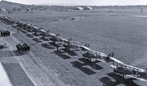 Elever ved flyskolen marsjerer. Tiger moth-fly står oppstilt. 1930-tallet. KFF-foto