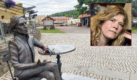 HÆRVERK: Kunstner Nina Nesje (innfelt) er svært lite fornøyd med at noen limte fast et trekors (se i den røde sirkelen på bordet) på statuen hun har laget av Jahn Teigen.