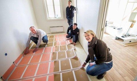 SENSORGULV: Dette smarte gulvet ble installert i visningsleiligheten på Holmen i 2013. Målet er at flere beboere skal få et slikt som en del av en trygghetspakke. Gulvet har sensorer som varsler hjemmesykepleien om beboeren beveger seg i leiligheten sin. Fra venstre: Palle Stevn (Marimils), Lars Lystad (Smartec) og Wenche Halvorsen (kommunen). Stående ser vi Webjørn Hageselle (Lions Fredrikstad).