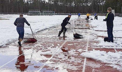 SNØRYYDING I SLUTTEN AV MAI: Alta IFs friidrettsgruppe har jobbet hardt med å få den nye løpebanen på Aronnes fri for snø og klar til åpningsstevne på lørdag. Søndag settes det ny deltakerrekord på den nye løpebanen på Alta idrettspark. Foto: Alta IF Friidrett