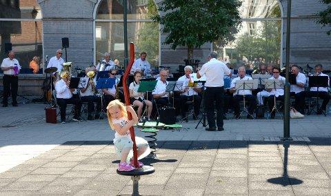 GLADE TONER: Korpsmusikk og lek passer bra sammen på en solfylt lørdag i Hønefoss sentrum.