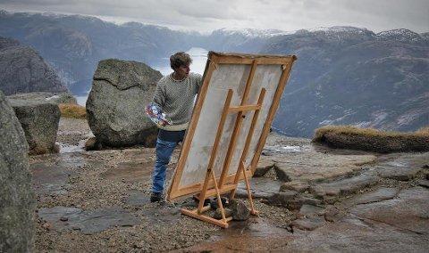 I ARBEID: Stian Heimlund Skjæveland fikk gjort mye arbeid på maleriet sitt da han tok turen til Preikestolen. Nå står andre motiv i Lysefjorden for tur. (Foto: Privat)