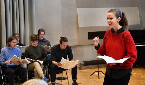 STORT VERK: Lærer og dirigent Anne-Lise Sydnes varmer opp elevene. Mozarts «Requiem» har stått på timeplanen i hele høst.