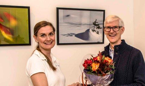 Ivar Ola Opheim, webredaktør i Ås kommune, stiller ut fotografier i venterommet hos Ås Helse. Her får han blomster av kiropraktor Ingrid Cowie.