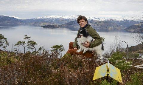 TA EIN PAUSE! Sverre Stakkestad, her med hunden Eddie, midt i kulturstien på vegen inn til Mælen og med utsikt til Kvamsøy der oppdrettsanlegget i Fyksesund skal flyttast. I tillegg er det søkt om eit nytt anlegg mellom Kvamsøy og Mælen, 500 meter frå land. Foto: Mette Bleken