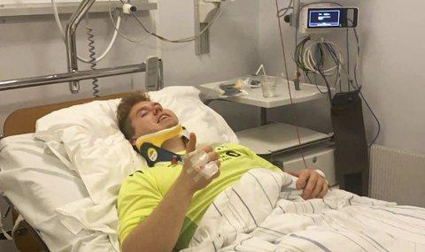 TOMMEL OPP: Sebastian Jarnæs med keeperdrakta på i sykesenga på Vefsn sykehus. Keeperen fikk hard medfart i en duell, og fikk kraftig hjernerystelse. – Det kunne gått mye verre hvis jeg hadde blitt truffet litt lenger ned mot nakken, sier han. Foto: Privat