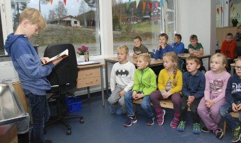 Høgtlesing: Steffen Loberg les frå boka si, medan elevane i fyrste klasse (fremst) og i andre klasse ved Rogne skule fylgjer med.