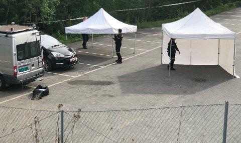 ÅSTEDET:Kriminalteknikere rigger seg til på parkeringsplassen på baksida av Elkjøp på Bjertnestangen der en mann torsdag morgen ble funnet død i den svarte bilen på bildet.