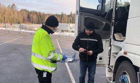 Roger Gulvik fra Statens vegvesen får dokumenter av sjåfør under kontroll på Svinesund.