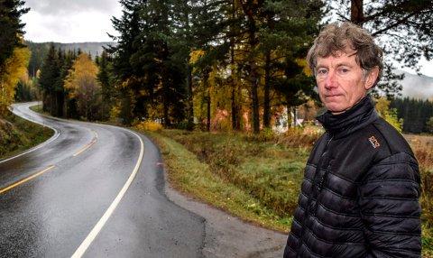 ULYKKESSVING: - Det bør vurderes å sette opp autovern langs Nerlaussvinga, mener nabo Sverre Trætteberg. Søndag landet ulykkesbilen hvor en mann i 60-årene fra Land omkom, på taket nede ved huset hans i bakgrunnen.