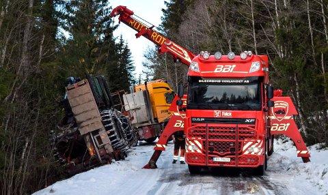 BILBERGING: To bergingsbiler jobber med å få lastebilen med skogsmaskinen bakpå opp på veien igjen.