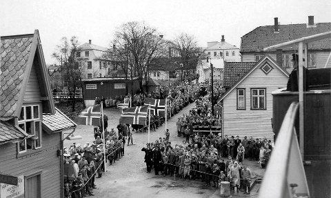 HER KJEM KONGEN: «Sunnfjord» legg til kai i Florø med Kong Olav på bruvengen. Politimenn gjer honnør ved tausperringane som lagar gate for Kongen når han går i land.