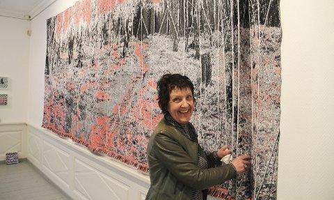 Åpner i aamodtgården: Tone Hellerud med sitt fem meterlange digitale tekstilarbeid som er kalt «Writing to wood». foto: kari Gjerstadberget