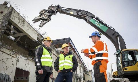 KNUSER: Formann på rivningstomta Vegard Wangen i Ragn Sells Miljøsanering AS forklarer Tordar Sætheråsen, til venstre, prosjektleder hos KK-Eiendom, og byggeleder Arne Nytrøen om betong         knuseren i bakgrunnen.