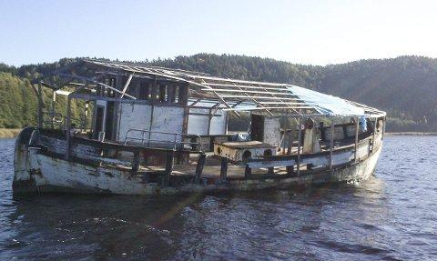 PÅ GRUNN: I over to og et halvt år har denne fiskebåten stått fast på en mudderbanke i Indre Iddefjord – Enningdalselva naturreservat. Nå ønsker Fylkesmannen Halden kommunes hjelp til å få det fjernet.