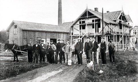 SKOGVEIEN. Fra nybyggertiden i vestre del av Nanset omkring 1910. Håndverkerne, som har tatt oppstilling på tvers av Skogveien, hadde under oppføring hjørnehuset mot Nansetveien, det som skulle bli Leinæs' bakeri. Det var et av de siste sveitserhusene her oppe, for nå hadde jugendstilen slått igjennom i trehusarkitekturen.