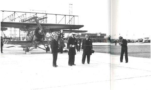 Lørdag 29. mai 1937 klipper Kong Haakon 7. den røde snoren og erklærer flyplassen for åpnet. Til venstre for Kongen står Stavanger-ordfører M. M. Michaelsen, mens skipsreder og formann i Stavanger lufttrafikkkomité, Ole Bergesen, står til høyre. Flyet bak er en av Hærens Fokkere.
