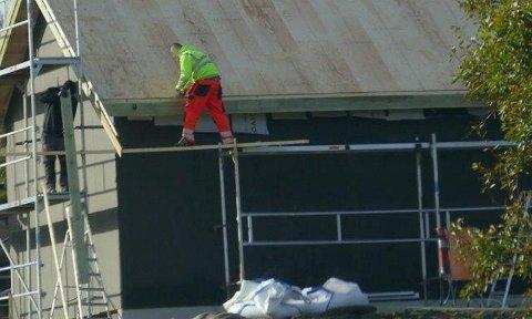 Her balanserer en arbeider på en smal planke mens han arbeids i høyden. Bildet er fra Austevoll.