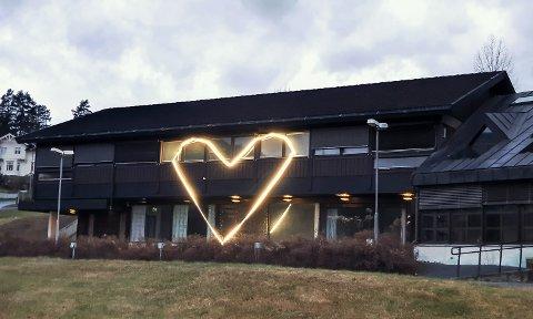 LYSER OPP: Et stort hjerte lyser opp fasaden på Sentrumsgården i Prestfoss.