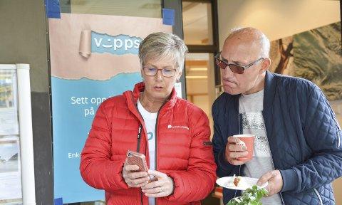 Vipps: Birgit Åsnes i Sparebanken Vest visar ein kunde korleis han skal bruka appen. Laurdag selde banken kake, lappar og kaffi til ei krone, så lenge kundane betalte via Vipps.