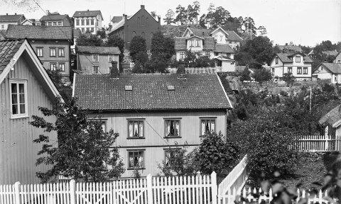 Smedsbukta i 1930-årene: Eldre bilder gode bilder tatt fra spesielle vinkler er alltid artig å finne. Som dette fotografiet som trolig er tatt noen år før krigen. Fotografen har stått i Smedsbulkta og sett opp mot husene langs Fjellmannsveien. Det første man drar kjensel på er endeveggen på Frikirken, bak sees furutrærne på Liselund. Husene kommer veldig godt fram.