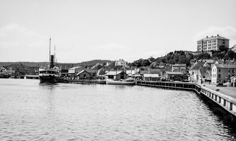 Dampskipsbrygga og Jernbanekaia: Fotografen har stått om bord i en båt som har ligget fortøyd på Jernbanekaia for å få tatt dette bildet. Fotografiet viser også at Jernbanekaia er relativt ny. Den sto ferdig på slutten av 1920-årene. Ved Dampskipsbrygga ligger en av Kystrutas båter son nettopp har lagt til brygga. Bildet er antakelig tatt før krigen.