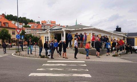 STOR PÅGANG: Lørdag ettermiddag var det lang kø utenfor Vinmonopolet i Kragerø.