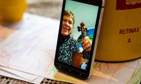 Pedagog Tone Amundsen Stokland følger med via mobiltelefonen og gir oppmuntrende tilbakemeldinger, ris og ros.