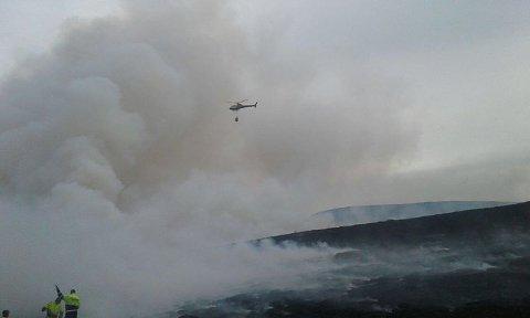 HELIKOPTER: Brannvesenet har fått bistand fra et brannhelikopter. Det skal være rundt 30 mål lyng og mose som er brent ned.