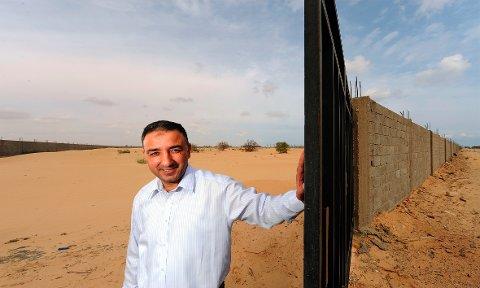 STOPPET OPP: I dag passer væpnede vakter på det som er grunnmuren til Jotuns nye anlegg i Libya. Her viser Yousef Abdulaziz, den gang salgssjef, fram tomta i 2009, før byggingen startet. Året etter bildet ble tatt startet den arabiske våren. Foto: Jotun