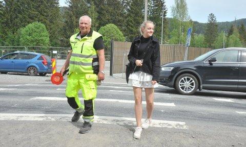 MOTSLUTTEN:Trafikkvakt Helge Klemp følger niendeklassing Isabel Eriksen Flatbye (14) trygt over riksveien etter endt skoledag på Hakadal ungdomsskole mandag ettermiddag. Senere i uka stenges den midlertidige overgangen for godt.