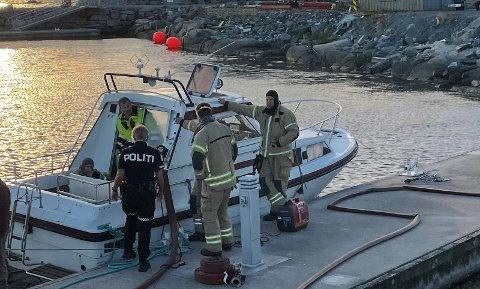 RYKKAR UT: Brannvesenet pumpar vatn ut av fritidsbåten.