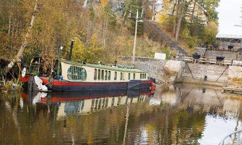 VED SLUSENE: Her ved slusene på Ørje ligger husbåten «Christofine». Her har den hatt sin faste plass siden 2011. Båten er bolig for samboerparet Hein Hoogstad og Solfrid Moen.