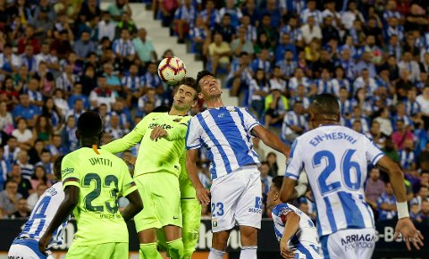 FC Barcelona's Gerard Pique, top left, duels for the ball against Leganes' Mikel Vesga during the Spanish La Liga soccer match between Leganes and FC Barcelona at the Butarque stadium in Leganes, Spain, Wednesday, Sept. 26, 2018. (AP Photo/Manu Fernandez)