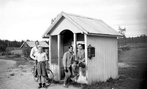 TREFFSTEDET: Denne dagen i juli 1937 var kiosken til Halvdan Danielsen et møtested og treffpunkt, akkurat som de fleste andre dager. Mannen på sykkel er Håkon Brenna, og foran ham Ole Røkholt. De dresskledde karene er feriegjester fra Oslo. Den ene ved navn Audun, og mannen lengst til høyre er Kjell Anker Hansen, en kar som gjorde seg bemerket i fotball, og blant annet ble norgesmester med Skeid i 1947. (Bilde utlånt av Nordre Odalen Kulturlag)